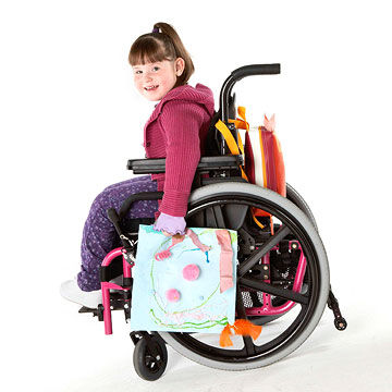 child sitting in wheelchair smiling